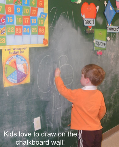 boy drawing on chalkboard wall